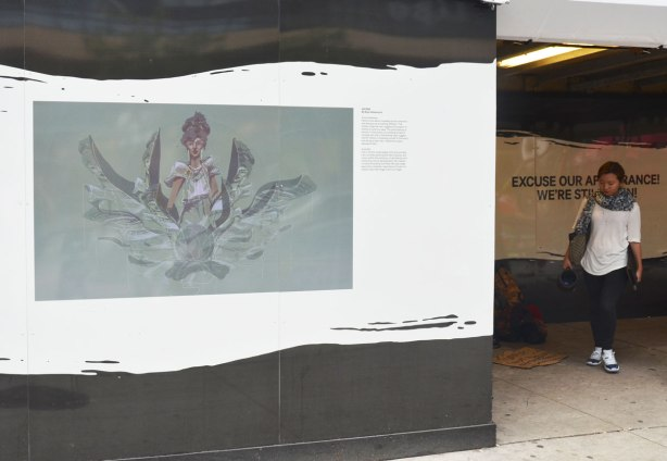 A woman walks around a corner and is approaching a wall with a picture on it called 'Ascend'