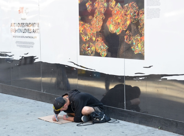A man is sitting on the sidewalk. He is making a sign on a piece of brown cardboard. The wall behind him has a large picture on it that is part of an exhibit