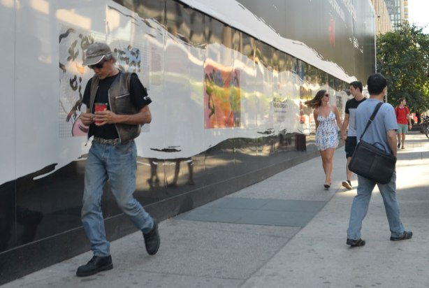 People walk by the hoardings beside the sidewalk on Dundas St. near Yonge, part of the new H & M store being built there. There are pictures on the wall.