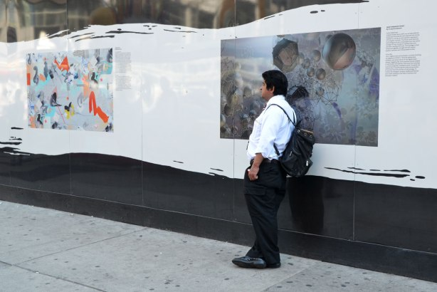A man in a white shirt and wearing a backpack leans against a white wall that has a picture printed on it.
