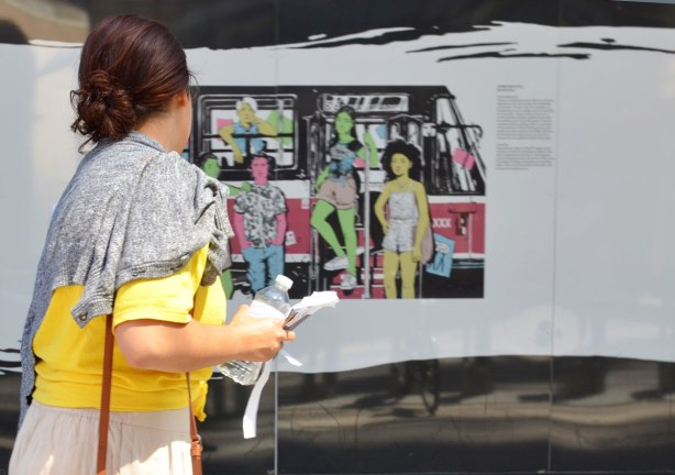 A woman walks by a wall that has a picture on it os people getting off a streetcar. The woman is looking at the picture