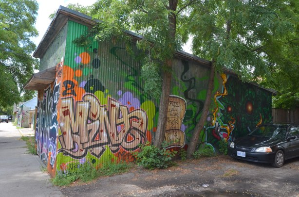 The side of a garage door in summer, two trees and a parked car.  The side of the garage is covered with street art