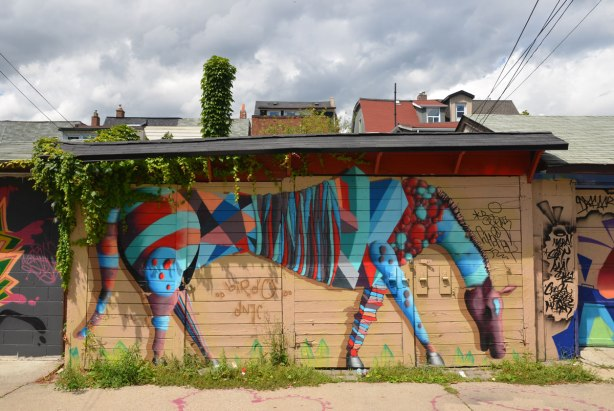 A painting by street artist birdo of a red and blue striped horse like creature with its neck bent downwards so that it looks like it is eating the weeds that are growing between the cracks in the lane.  It is on a garage door, tops of houses can be seen in the background, above the garage