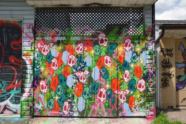 A garage door in an alley that has been painted with many brightly coloured skulls