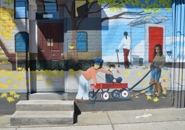 part of mural that depicts a street scene - two kids are playing on a red wagon, a woman is walking a dog and a woman with a cane is waiting at a bus shelter.