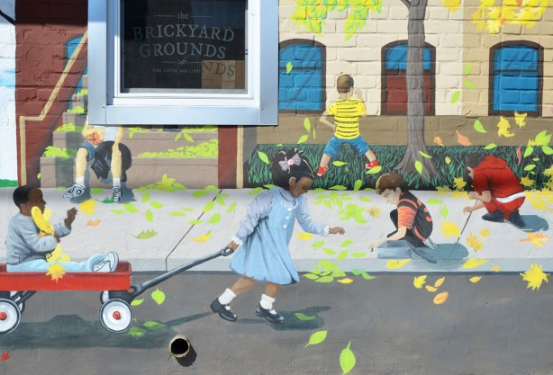 part of mural that depicts a street scene - a little girl pulls a boy in a red wagon while other kids are playing on the sidewalk