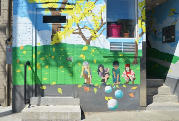 part of mural that depicts a street scene - four kids are playing marbles