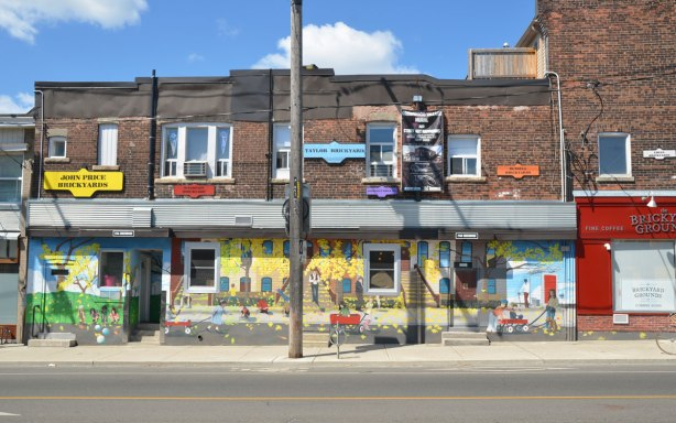 looking across the street to a row of brick store fronts, two storeys high.  The bottom storey has been painted with a mural that has a yellow background.