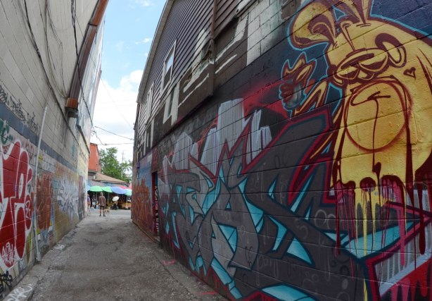 looking down the alley, wide angle shot, poser bunny mural on the right side, red tag graffiti on the left.  At the end of the alley a man stands with his dog, a woman with a white umbrella is passing by