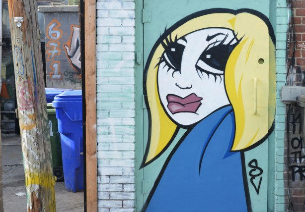 Graffiti Alley - on a light turquoise door, a stylized painting of a woman with yellow hair, red lips, blue dress, long black eye lashes