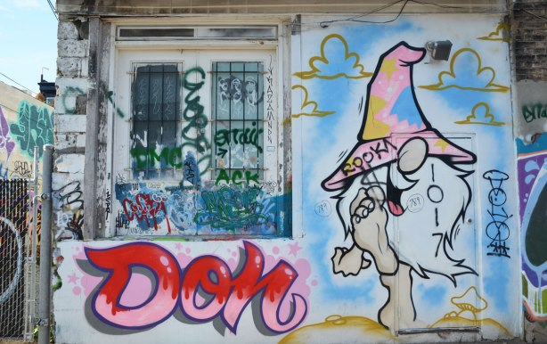 Graffiti Alley - a wall with a window on one side. Under the window is written the word Don in large pink and red letters. Beside the window is a painting of a man with a pointy top hat that covers his eyes, he has a big nose and a large white beard.