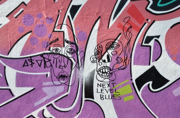 Graffiti Alley - two black line drawings of faces that have been drawn on top of a pink and purple street art painting.