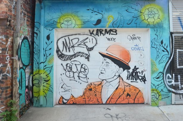 painting on a garage door - older man with orange jacket and orange bowler hat.  Around the garage door are flowers on a blur background.
