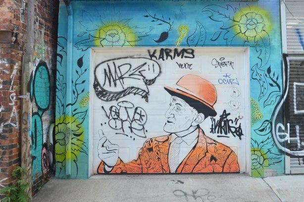 painting on a garage door - older man with orange jacket and orange bowler hat.  Around the garage door are flowers on a blur background.