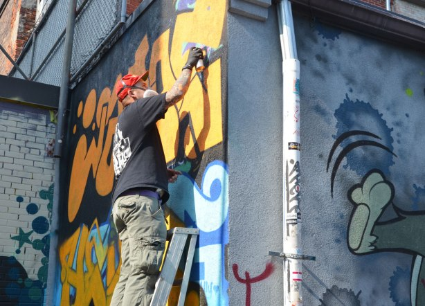 Graffiti Alley - man on ladder spray painting a street art piece