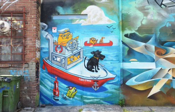 Graffiti Alley - uber5000 mural of a boating scene, yellow bird sterring a boat, black dog sitting on the bow, another yellow bird paddling a red canoe