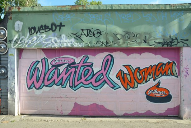 Graffiti Alley - garge door painted in two shades of pink with the words Wanted Woman Gotham painted on the garage door as well
