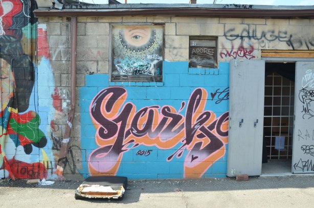 Graffiti Alley - part of a wall painted light blue with the word Yarka painted in purple and orange script