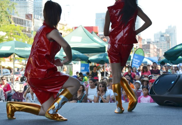 Two girls wearing shiny red dresses and gold and silver boots perform a dance on an outdoor stage. The audiencee is in the background