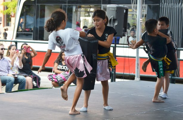 Four kids, two girls and two boys, practice kicking as part of a muay thai demonstration on an outdoor stage at a festival