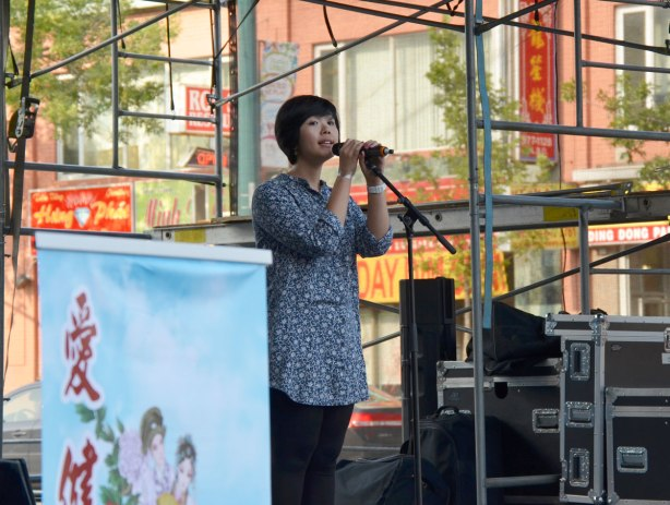 A chinese woman sings on an outdoor stage at the Chinatown festival on Spadina Ave