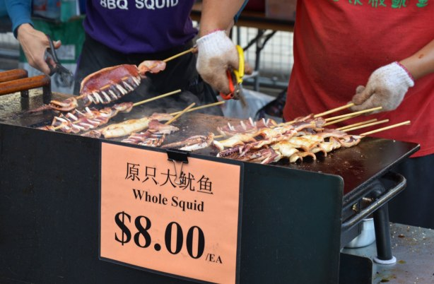 Fried squid on sticks being barbecued at a street festival