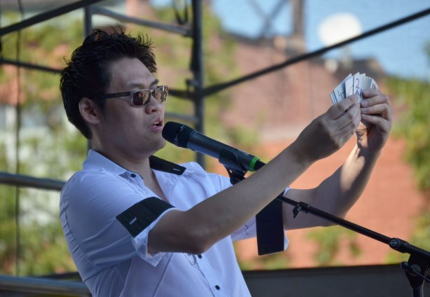 magician Stephen Cheung shows a deck of cards at an outdoor show