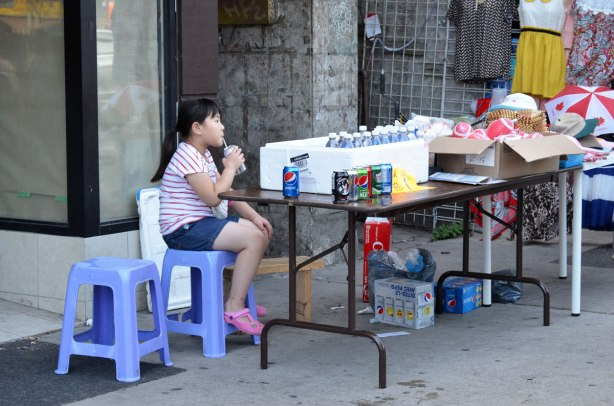 A girl tends a table full of cold drinks that are for sale, on the sidewalk