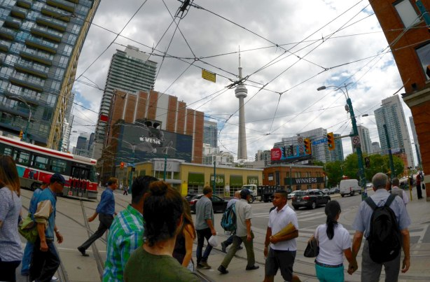 the intersection of King and Spadina in Toronto with a wide angle lens. People are crossing the street, there is a streetcar and lots of streetcar wires. THe LCBO and Winners are in the background as well as the CN Tower