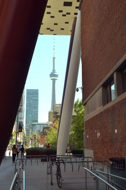 Looking through the pencil like supports to the black and white upper lever addition to OCAD (Ontario College of Art and Design). The CN TOwer and other tall toronto buildings are in the background.