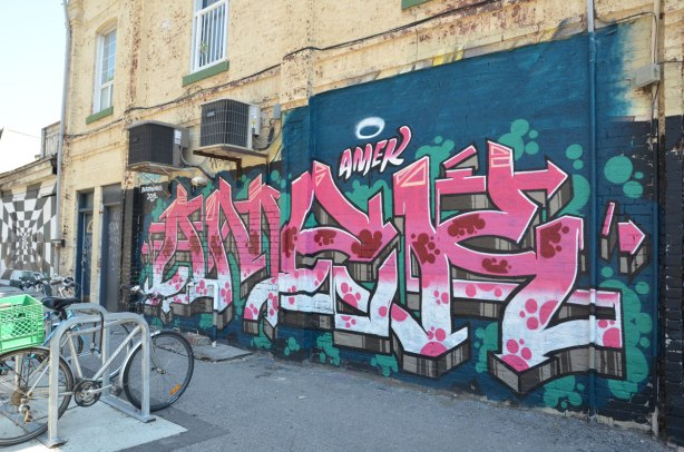 street art by amek in pink white on blue background, sidewalk and bicycles in front of it.