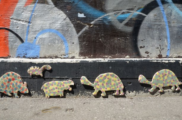 Little animals crawl along the bottom part of a wall in an alley. They are covered in polka dots, there are two turtles, a hippo, a dinosaur and part of a beaver