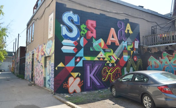 A wall in a parking lot is covered with a mural with large S A and K letters,