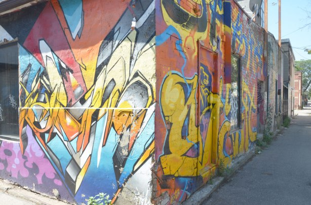 graffiti and street art on both side of a corner of a building at the intersection of two alleys