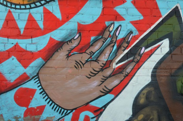 close up of a street art painting showing a large hand in front of a blue and red sweater