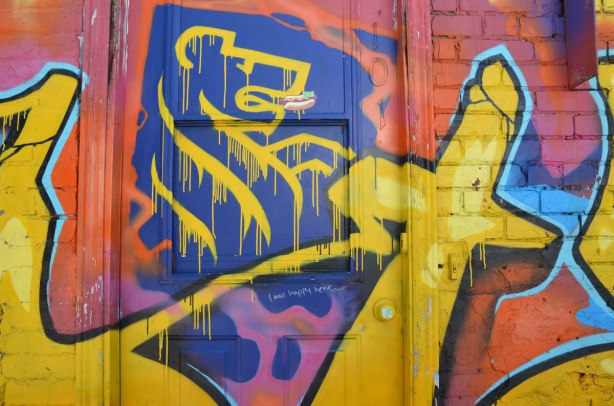 close up of a door covered with bright yellow, red, and blue graffiti