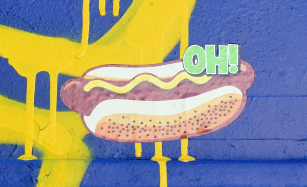 sticker graffiti, hot dog with line of mustard on it on a blue and yellow door