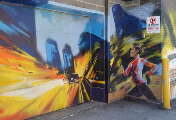 mural of a jogger and a car with bright headlights shining through the night