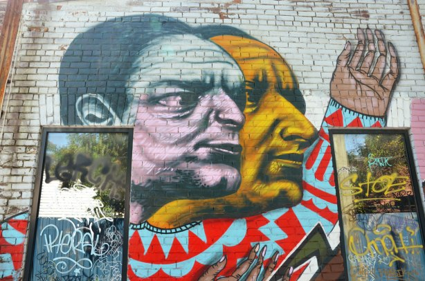 part of a street art painting on a wall with two windows, two large male faces, one in grey and pink and one in a brownish yellow