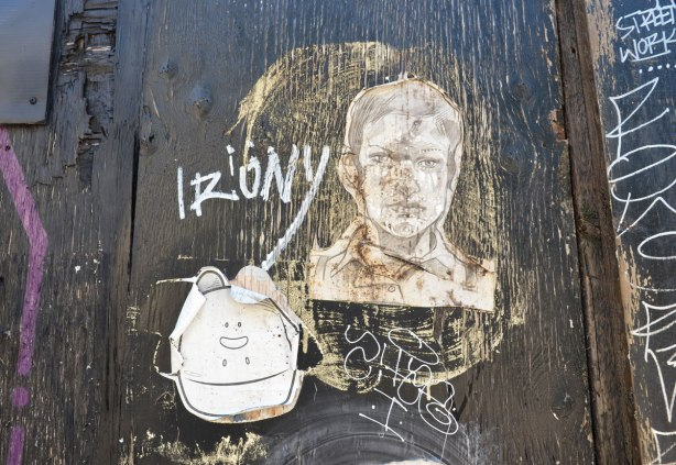two wheatpaste graffiti pieces, one yipyaps and one man's head.  The word irony is written as well.  They are on a worn black painted wood surface