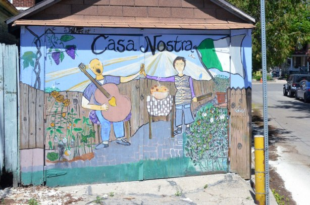 garage door with a picture on it titled Casa Nostra, a picture of a man playing a large guitar and a woman standing beside an outdoor table with food on it.