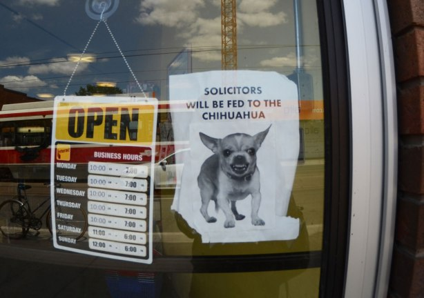 sign on the door of a store that says Solicitors will be fed to the chihuahua, with a picture of a little chihuahua dog below the words