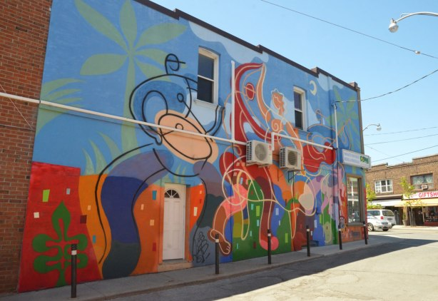 large colourful mural on the side of building, two stylized musicians, a drummer and a guitar player as well as two people dancing.