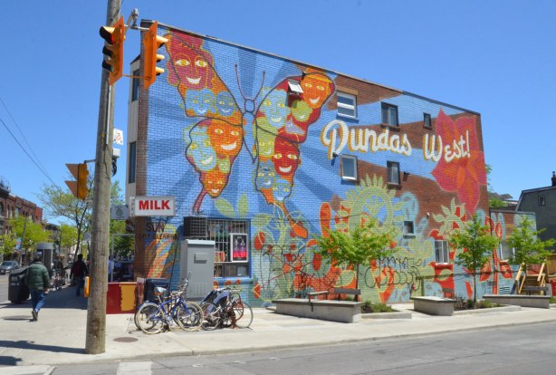 building on the corner of Sheridan and Dundas is a two storey brick building. On the whole of the side wall is a large Dundas West mural featuring a large butterfly painted on it.