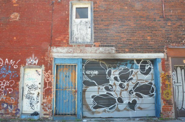 blue door with faded paint and a metal grille in front of it, beside a garage door with graffiti on it including the words Idle no more. Upper storey has an exterior door that goes nowhere