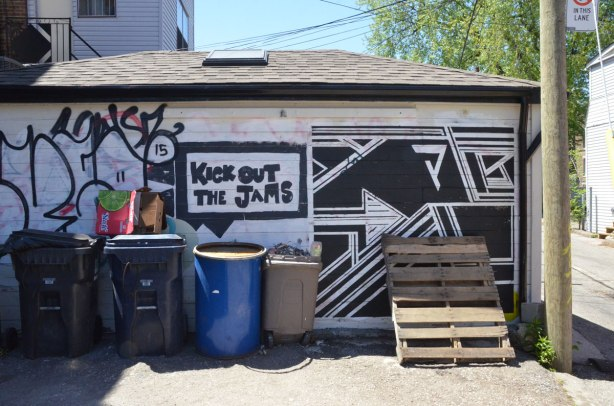 black and white street art on a garage door that is partially obscured by trash bins and wooden structure.   The art is geometric shapes and includes the words Kick out the Jams