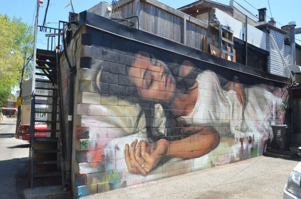 a Jarus street art painting of a woman sleeping on a bed. She has long black hair and is wearing white clothes