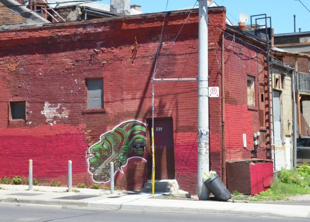 On a wall that has been painted a couple of shades of red is a painting of a green head with a green and red striped head dress on