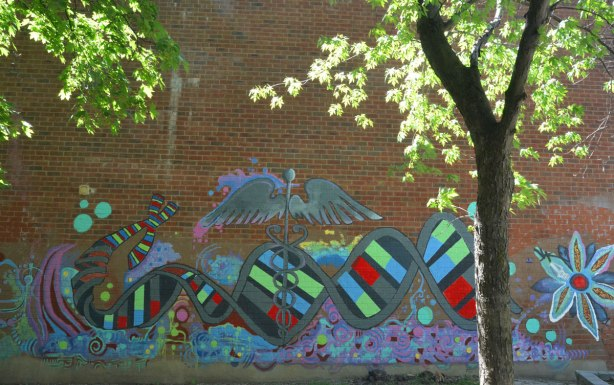 mural behind a small tree on a red brick wall, spiral of DNA, medical symbols, butterfly