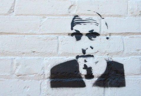 black stencil of a man's head on a white brick wall